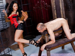 Naked villein guy stands still in front of black haired latin domina Kiara Mia. She makes him lick her legs and feet before she bares her biggest tits and big juicy ass. She spreads her big buttocks right in front of her villein man.