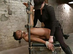 With her feet tied up and metal clamps all over her body the ebony slut endures a harsh punishment. This mistress knows what he's doing and gives her both pain and pleasure. She can't even scream as her mouth is folded with scotch tape. Look at that shaved pussy and how unfathomable she's rubbing it with the vibrator.