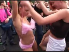 Chicks dance exposed in a large crowd outdoors