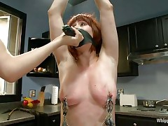 Odille has a strap on dildo attached on her face and with her hands tied and clamps on her nipples and pussy she waits patiently in the kitchen for the blonde milf to undress. After the blonde is naked, with a little help and guidance she insets the dildo in that shaved cunt, fucking it like a submissive slut.